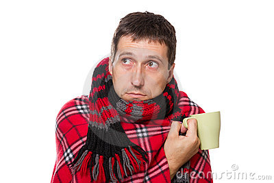 Cold man wrapped in blanket, holding mug