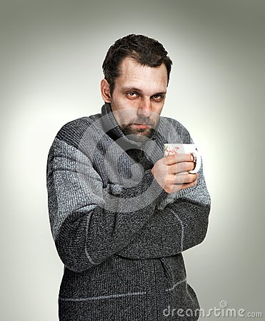Cold, sick man dressed in grey sweater holding a cup of tea in hands