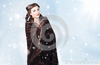 Cold young winter girl standing outdoor in snow