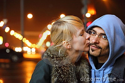 Coldly fall city. woman is kissing her man
