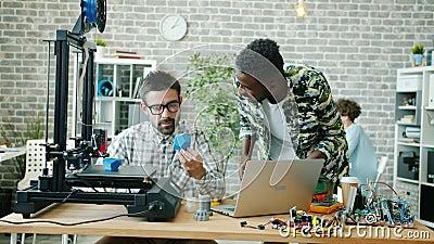Colegas jóvenes hablando en la oficina usando impresora 3d, tablet y laptop metrajes