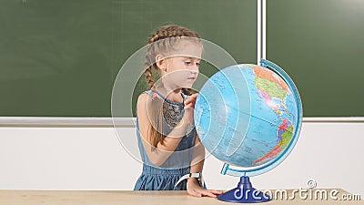Colegiala con el globo en pizarra de la sala de clase en fondo almacen de metraje de vídeo