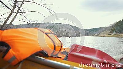 Colete salva-vidas no catamarã inflável e no barco de flutuação no fundo do rio video estoque