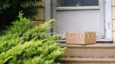 Colis de la livraison sur le porche de la maison L'homme étend la boîte près de la porte La distribution à la trappe banque de vidéos