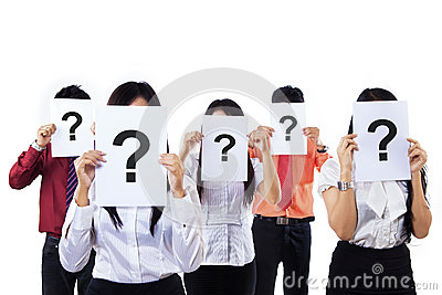 Colleagues holding question mark signs