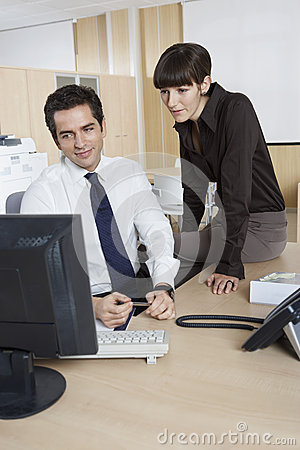 Colleagues Using Computer At Desk In Office