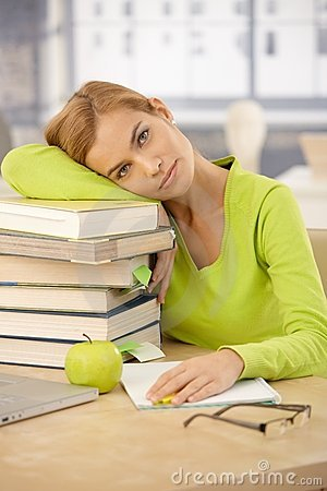 College girl relaxing with head on books