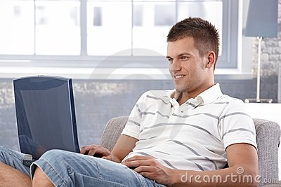 College student browsing internet at home smiling