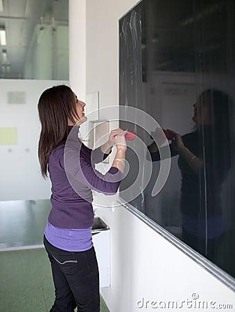 college student erasing the chalkboard