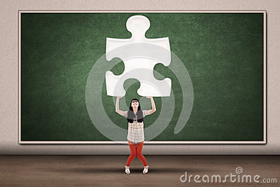 College student holding piece of puzzle