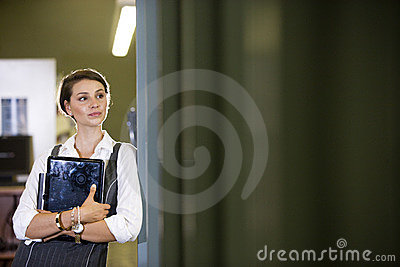 College student at library doorway holding laptop