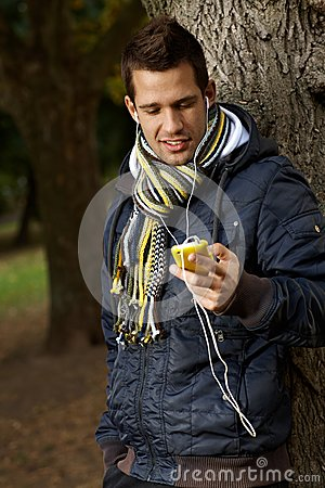 College student with mp3 player outdoors