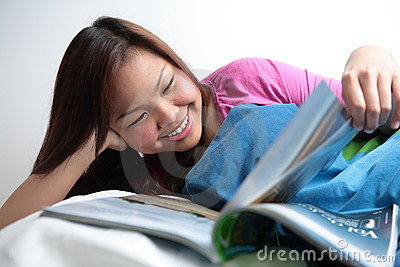 College student reading in her bed