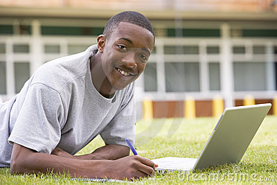 College student using laptop on campus lawn