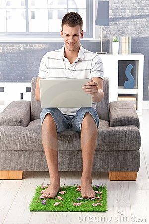 College student using laptop smiling at home