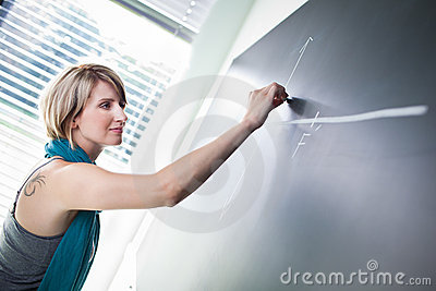 College student writing on the blackboard