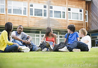 College students sitting and talking on lawn
