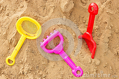 Color plastic toys on a sand