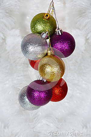 Colored Christmas balls on a white tinsel