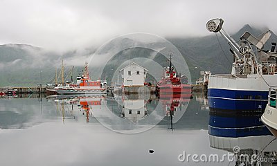 Colored fishing boats with fog - Honningsvag Harbour - Norway Editorial Stock Photo