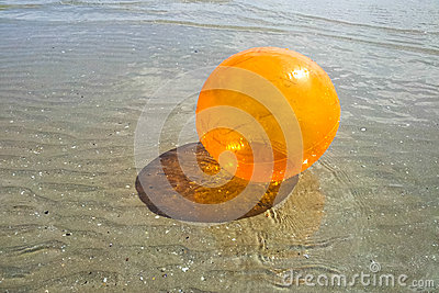 Colored orange ball in water on beach