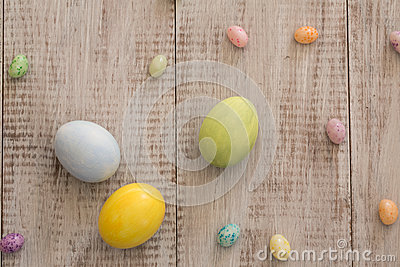Colored Painted Easter Eggs and Jelly Beans on White Wood Backgr Stock Photo