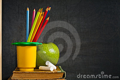 Colored pencil and green apple on old textbook