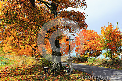 Colorful autumn Landscape with Crucifix and blue Sky