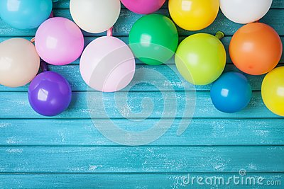 Colorful balloons on turquoise wooden table top view. Birthday celebration or party background. Festive greeting card. Stock Photo