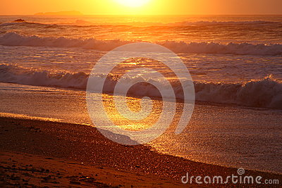 Waves rolling at beach by golden sunrise