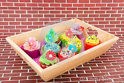 Colorful cupcakes on wooden tray