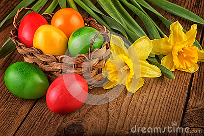 Colorful easter decoration with eggs in basket on dark wooden table Stock Photo