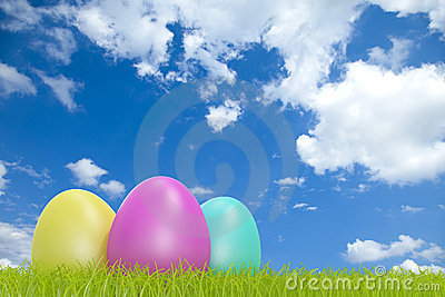 Colorful easter eggs in front of a cloudy sky with