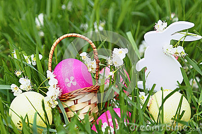 Colorful easter eggs, wooden rabbit and flowers on fresh spring grass in the garden. Stock Photo