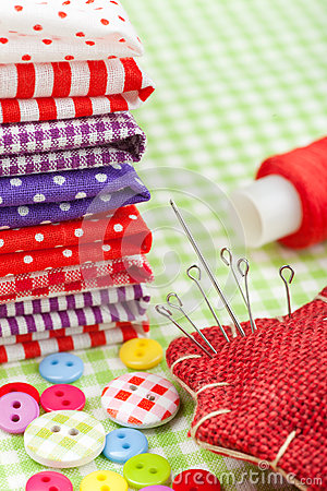 Colorful fabrics, buttons, pin cushion, thimble, spool of thread - set for sewing
