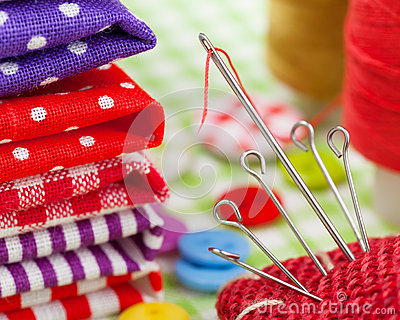 Colorful fabrics, buttons, pin cushion, thimble, spools of thread for sewing