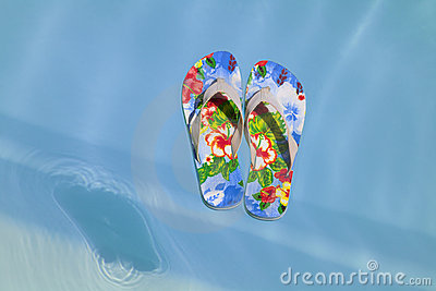 Colorful flipflops floating in a swimming pool