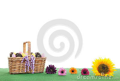 Colorful flowers and basket easter eggs on green grass Stock Photo