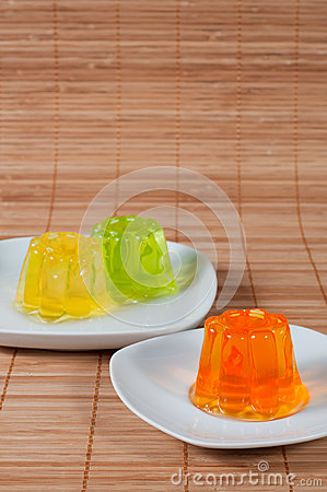 Colorful jelly on white plates over wooden background