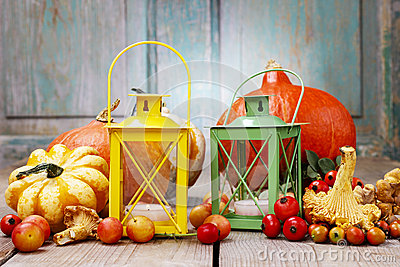 Colorful lanterns among autumn plants on wooden table