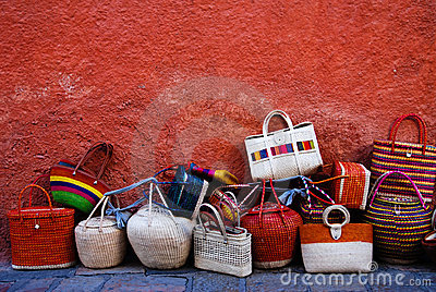 Colorful luggage and bags by a red wall.