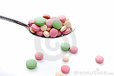 Colorful pills and spoon
