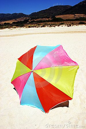 Colorful round umbrella on white sandy beach
