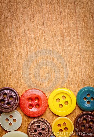 Colorful sewing buttons on a wooden background