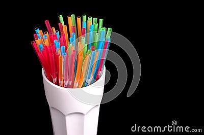 Colorful straws in white glass