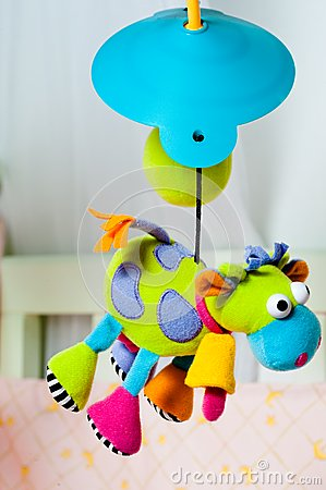 Colorful turning cow baby toy over the bed