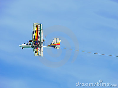 Colorful ultralight plane flying against blue sky