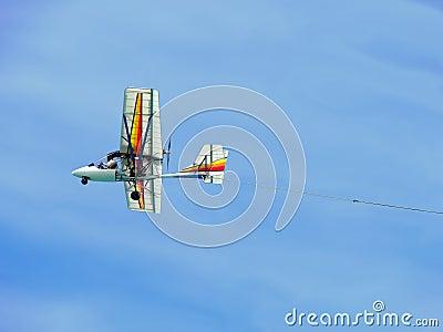 Colorful ultralight plane flying against blue sky