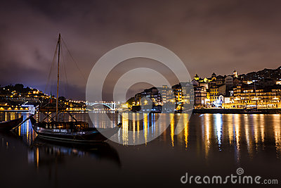 Colorful view of boats moored at twilight along the riverfront with lights reflecting in the Douro River Editorial Stock Photo