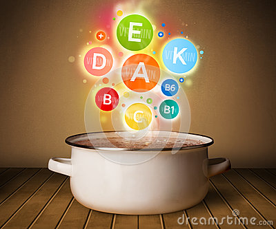 Colorful vitamins coming out from cooking pot Stock Photo
